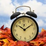 Retro clock on fall leaves sky background