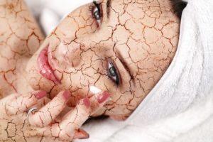 Woman applying moisturizing cream on her face